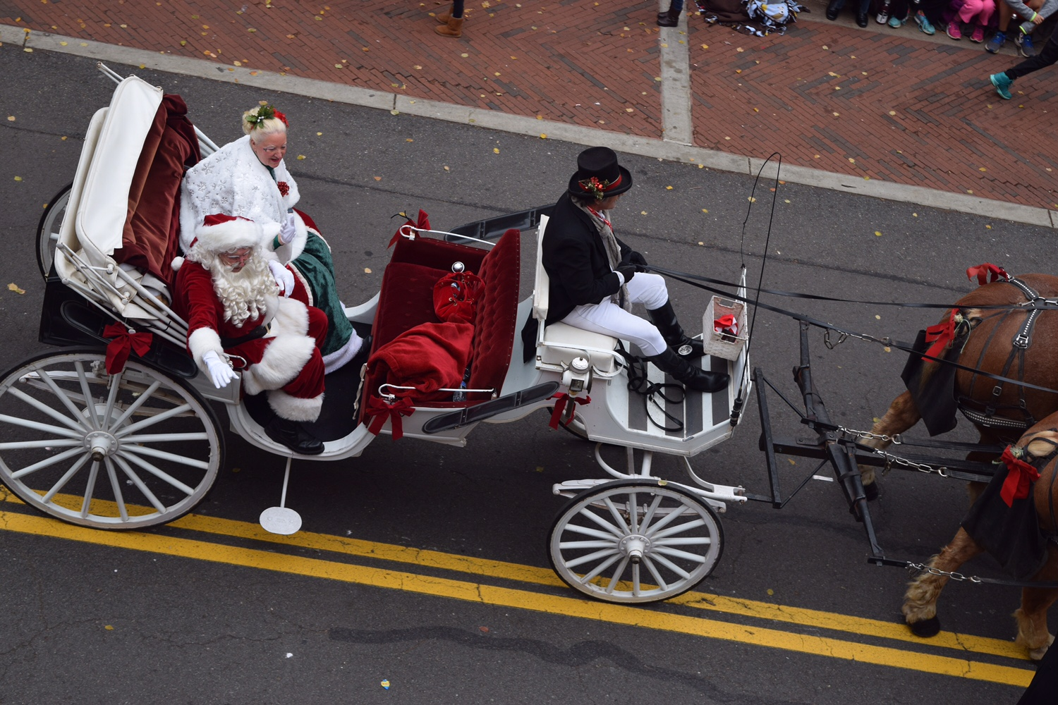 "People dressed up as Santa Claus and Mrs. Claus at the Reston Parade with their sleigh and ""reindeer"" (horses)."