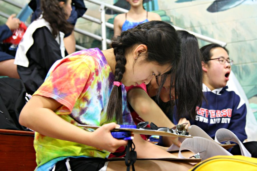 Freshmen+managers+Anne+Shen+and+Cynthia+Hu+prepare+to+keep+time+for+the+swimmers+during+the+meet.