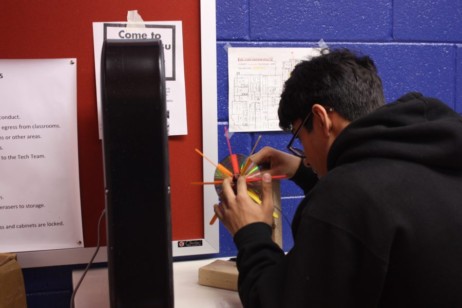 Science Olympiad team member Faaiz Memon perfects his Wind Turbine device in preparation for testing at the competition. By testing it now, he can modify and improve his design for future competitions.