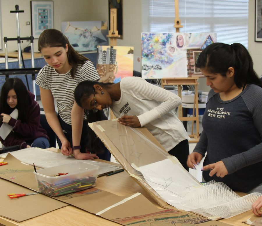 Art club members lay down preliminary sketches for mosaic to decide colors before creating the final product.