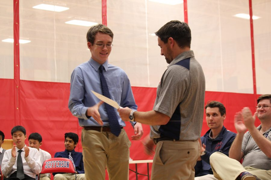 Jake Boltersdorf presents basketball player with a certificate.