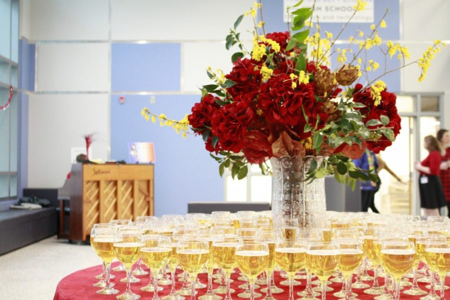 A table of drinks surround a bouquet of flowers while music plays in the background.