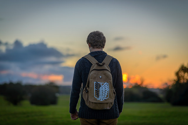A young man wearing an Attack on Titan backpack. Photo courtesy of Rowan Gillette-Fussell from Flickr.