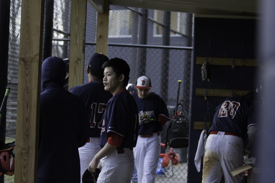 Players watch the game from the dugout.
