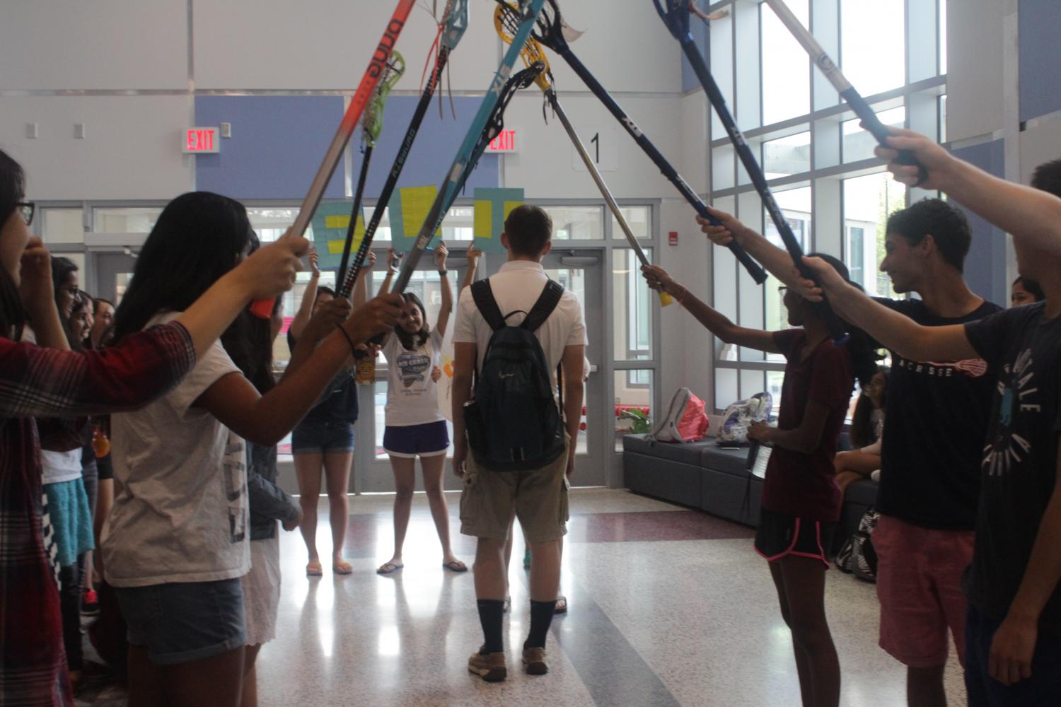 Lacrosse players hold up their sticks to make a pathway for Freshman Jessica Chen to ask Eli Kirtley to Sadies.