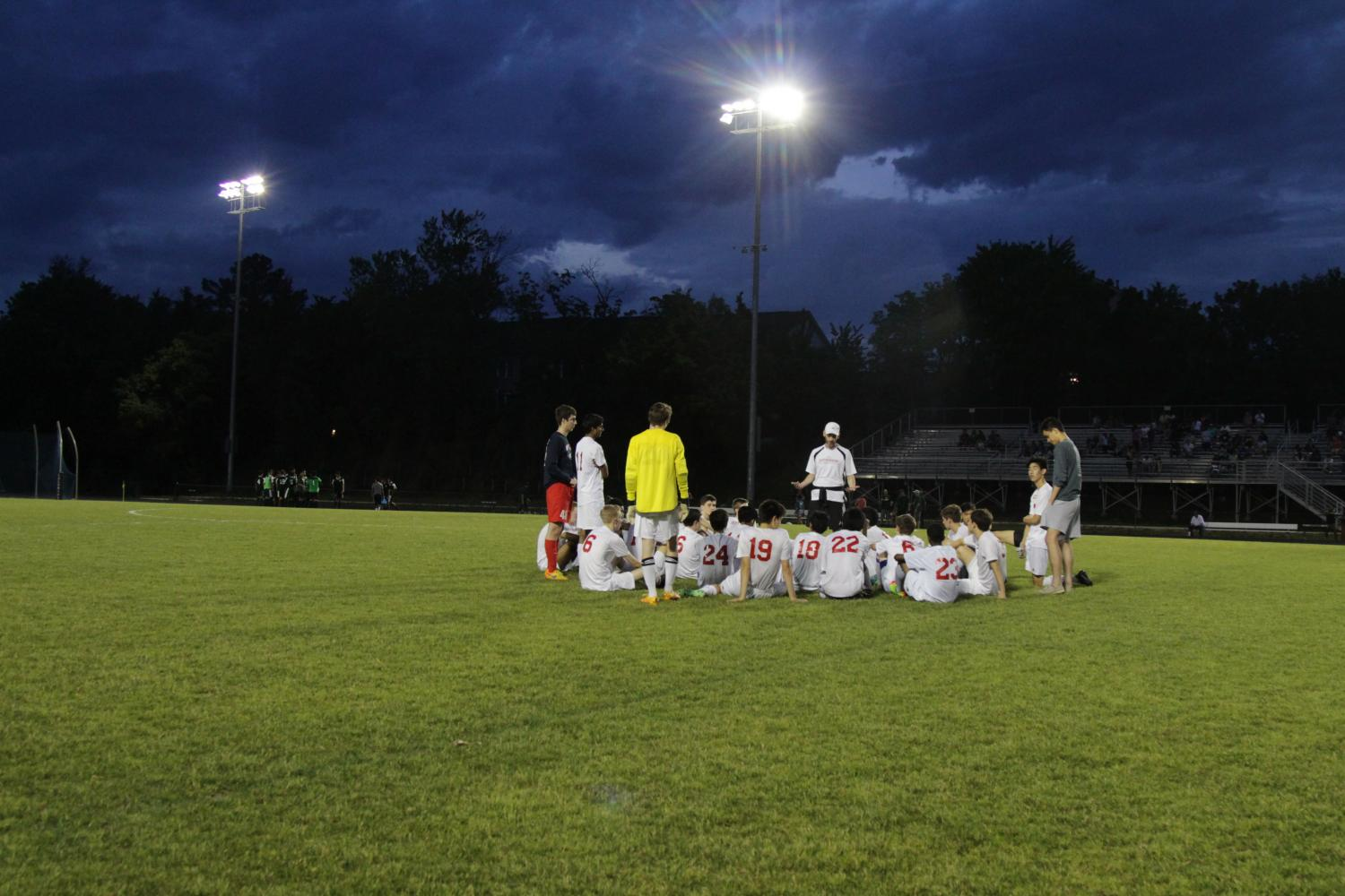 The boys soccer team get into circle with their head coach, Mr. Sean Burke, taking the lead in the discussion.