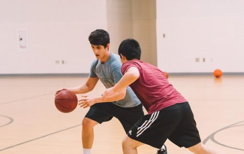Sophomore Abhishek Bazaz maneuvers around another player while playing an informal game of basketball.