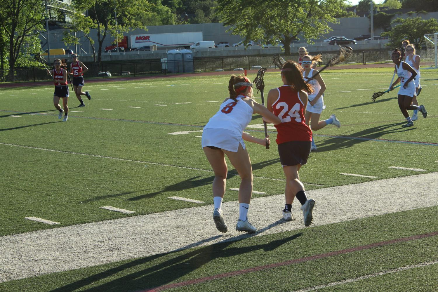 Marshall senior Rachel Piche guards Jefferson freshman Abby Kim as she runs with the ball toward the Marshall goal.
