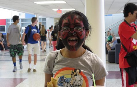Sophomore Ankita Vadiala grins with a Star Wars t-shirt, face paint, and an armful of food and drink.