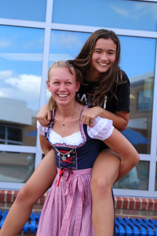 Sophomore Eva Decesare and German exchange student Emily spend their time in Oktoberfest sharing smiles and giving piggy-back rides.