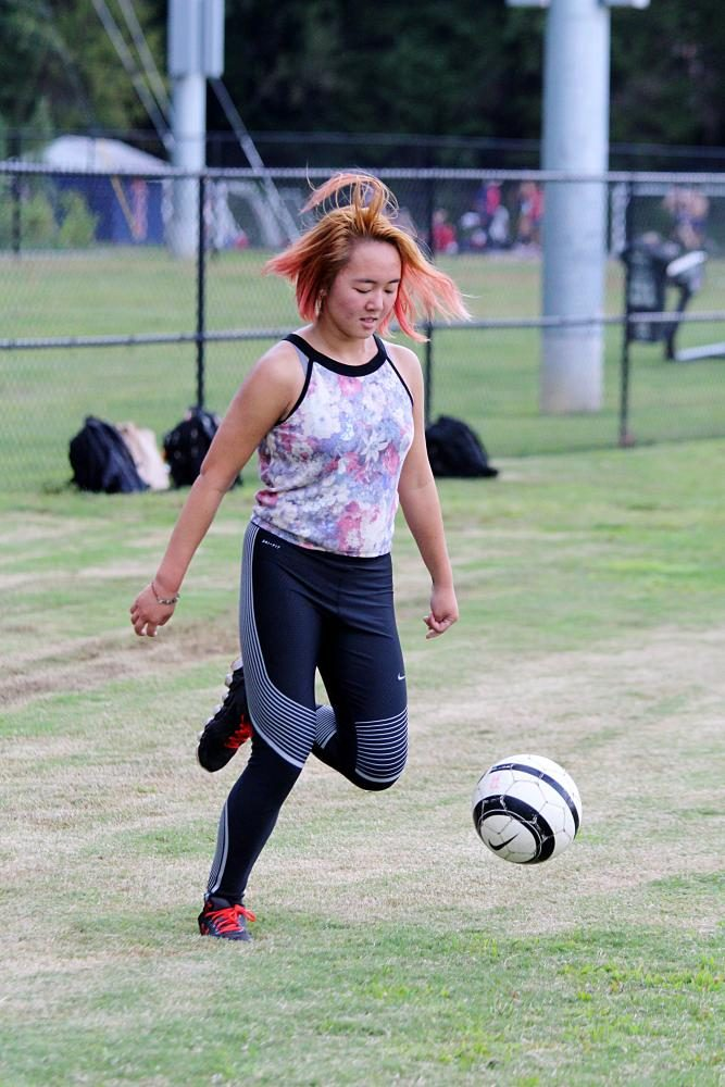 Junior Shay Le plays with a soccer ball in the baseball field.