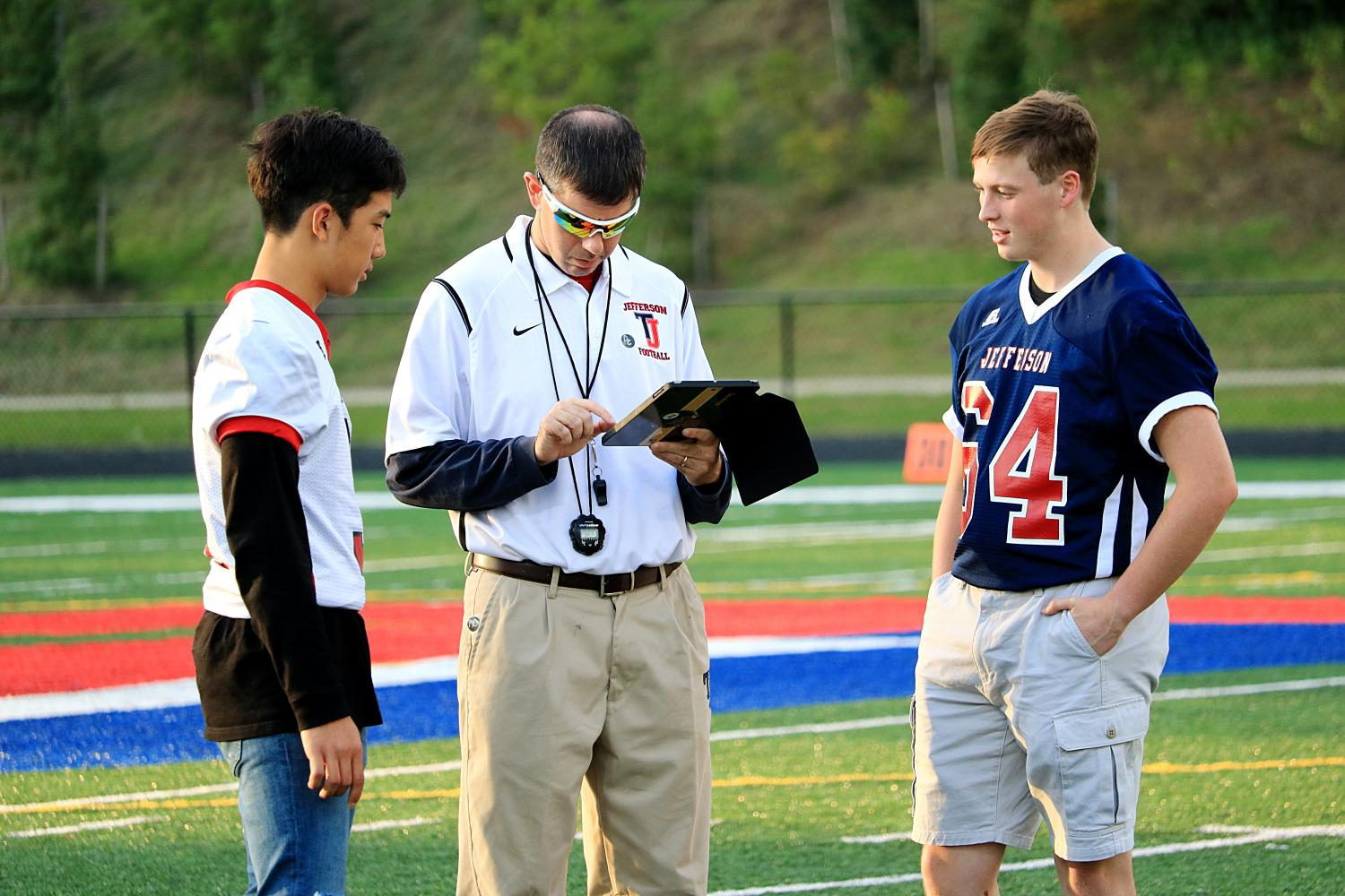 From left to right: Junior Jun Chong and Senior John Erskine discuss plans with teacher and football coach Michael Auerbach before the game starts.