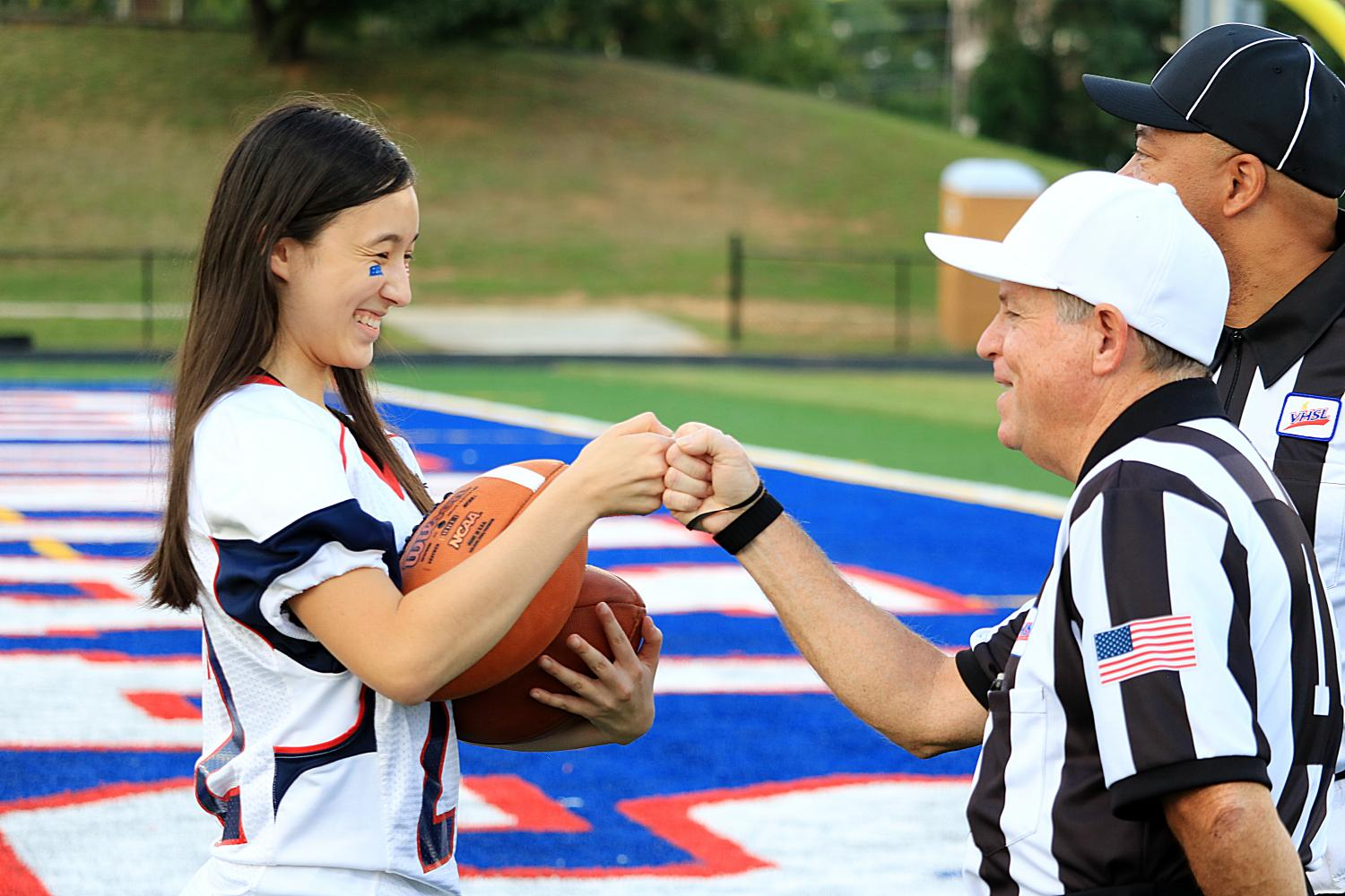 Senior Victoria Chuah fists bump one of the referees prior to the start of the game.