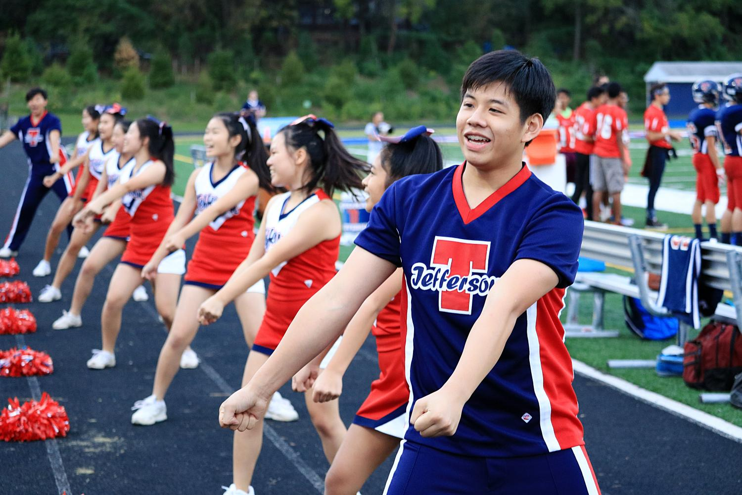 Cheerleader and junior Shawin Vitsupakorn performs cheers in front of the Jefferson crowd alongside other cheerleaders.