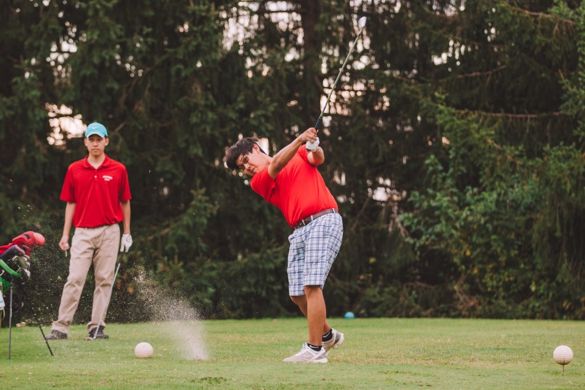 Senior Min Kang takes a swing and senior Richard Pan waits behind him for his turn at the tee during golf senior night on Sept. 14.  Kang has played golf for Jefferson since freshman year.