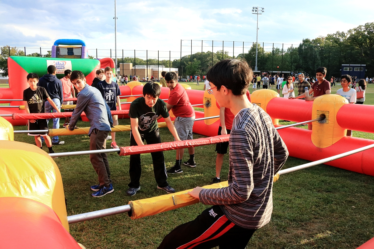 Students play human foosball in the baseball field.
