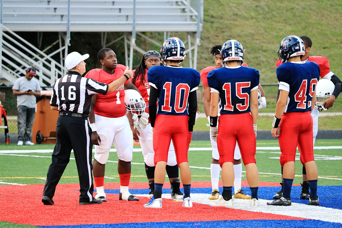 From left to right: Seniors Wonwook Do, Danny McCray, and Clayton Reppert stand in the center of the field for the coin toss at the start of the game.