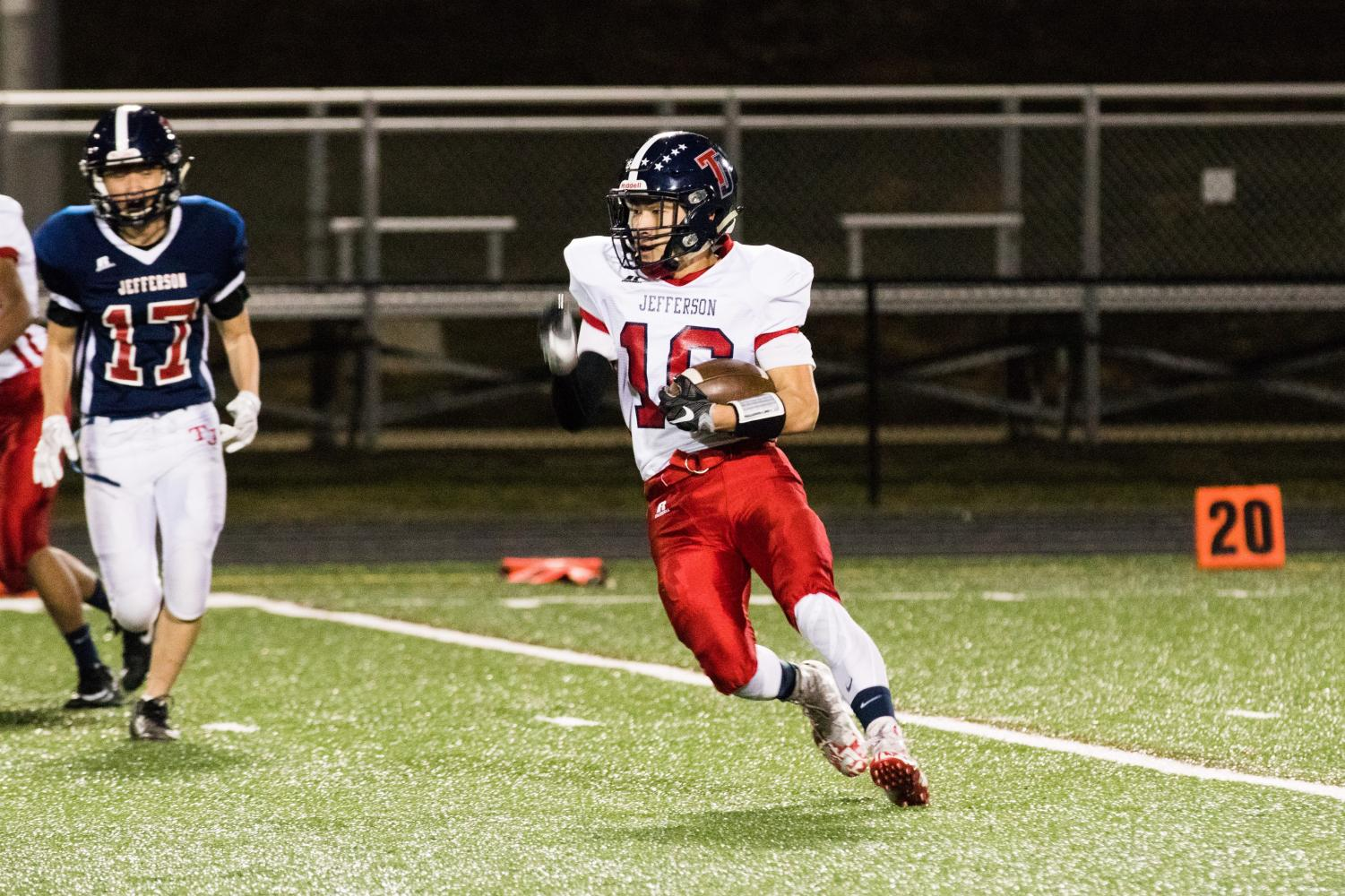 Junior Justin Kim makes a dash for the end zone, ball tucked in tightly under his arm, looking for a touchdown.