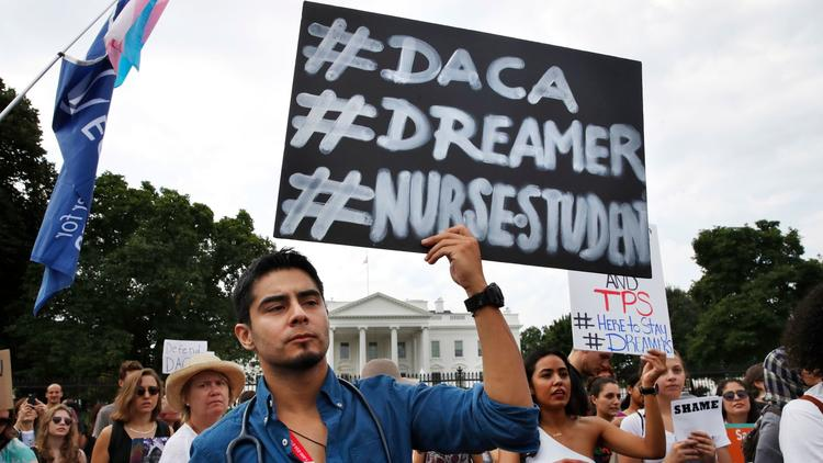 Photo courtesy of the Los Angeles Times. Carlos Esteban, a nursing student from Woodbridge, Va., protests with a group of people outside of the White House in support of DACA.