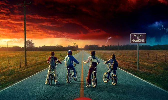 Mike (Finn Wolfhard), Dustin (Gaten Matarazzo), Lucas (Caleb McLaughlin), and Will (Noah Schnapp) look out over the horizon to confront the latest threat to Hawkins, Indiana.  Hawkins exists just near a parallel universe known as the Upside Down, from where monsters crawl into the town.