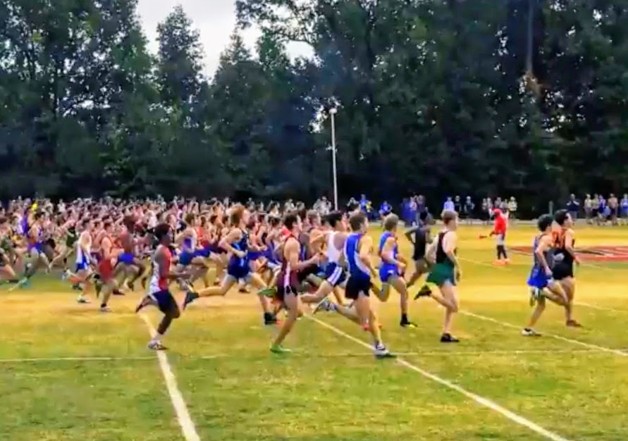 Runners competing in the varsity boys 5000 meter event, including 9 athletes from Jefferson, start the race as spectators cheer on.