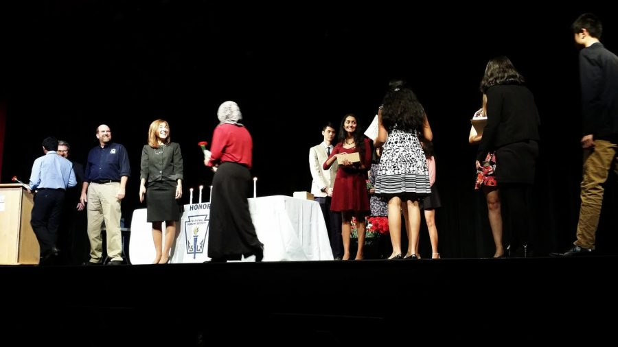 "Crossing the stage holding roses and certificates, students shake hands with speakers and officers. The inductees were sworn into the society during the evening ceremony. ""We just got inducted,"" junior Ritika Shrivastav said. ""I'm looking forward to it."""
