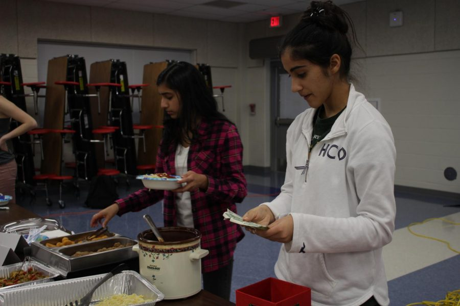 Junior Rhea Nandra checks payments. Nandra is a part of junior Nandhana Nair's group, which sold pasta with a variety of toppings.