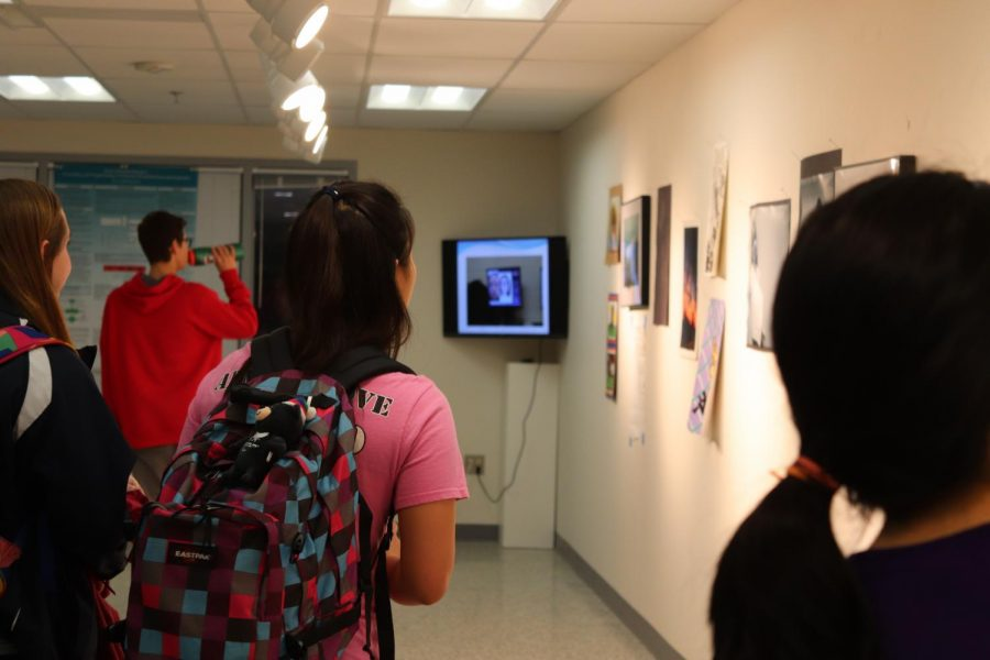 Students walk through the gallery.