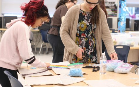 Sophomores and Art Club members Victoria Yang and Grace Cullen arrange glass tiles for the mosaic project. The club works on the project during weekly eighth period meetings.