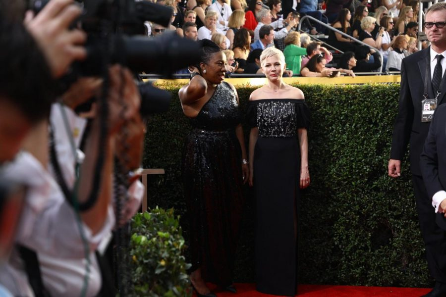 Burke, left, and Best Actress in a Motion Picture- Drama nominee Michelle Williams pose on the Golden Globes red carpet.