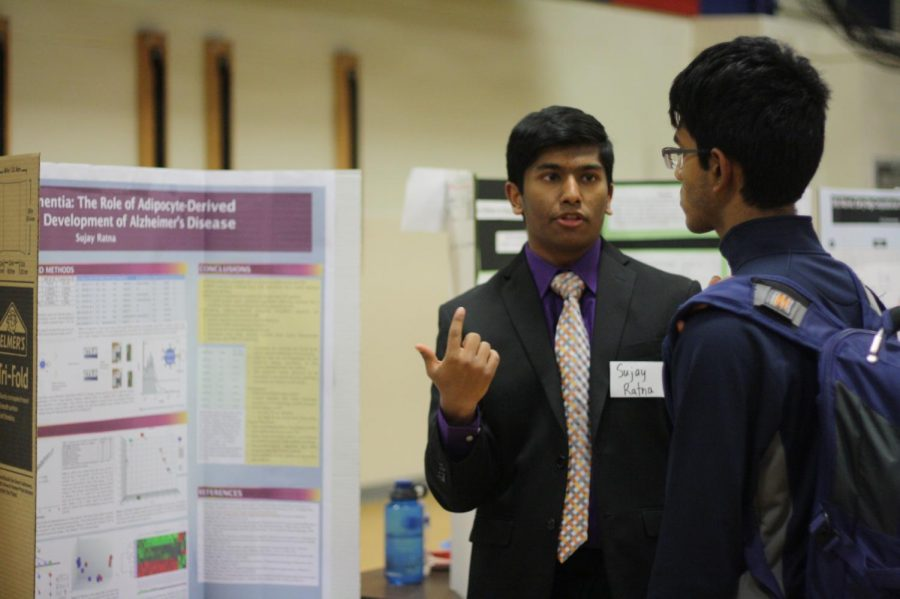 Pointing to his poster, senior Sujay Ratna presents his research to a student. Ratna's project won in the category of Cell and Molecular Biology.