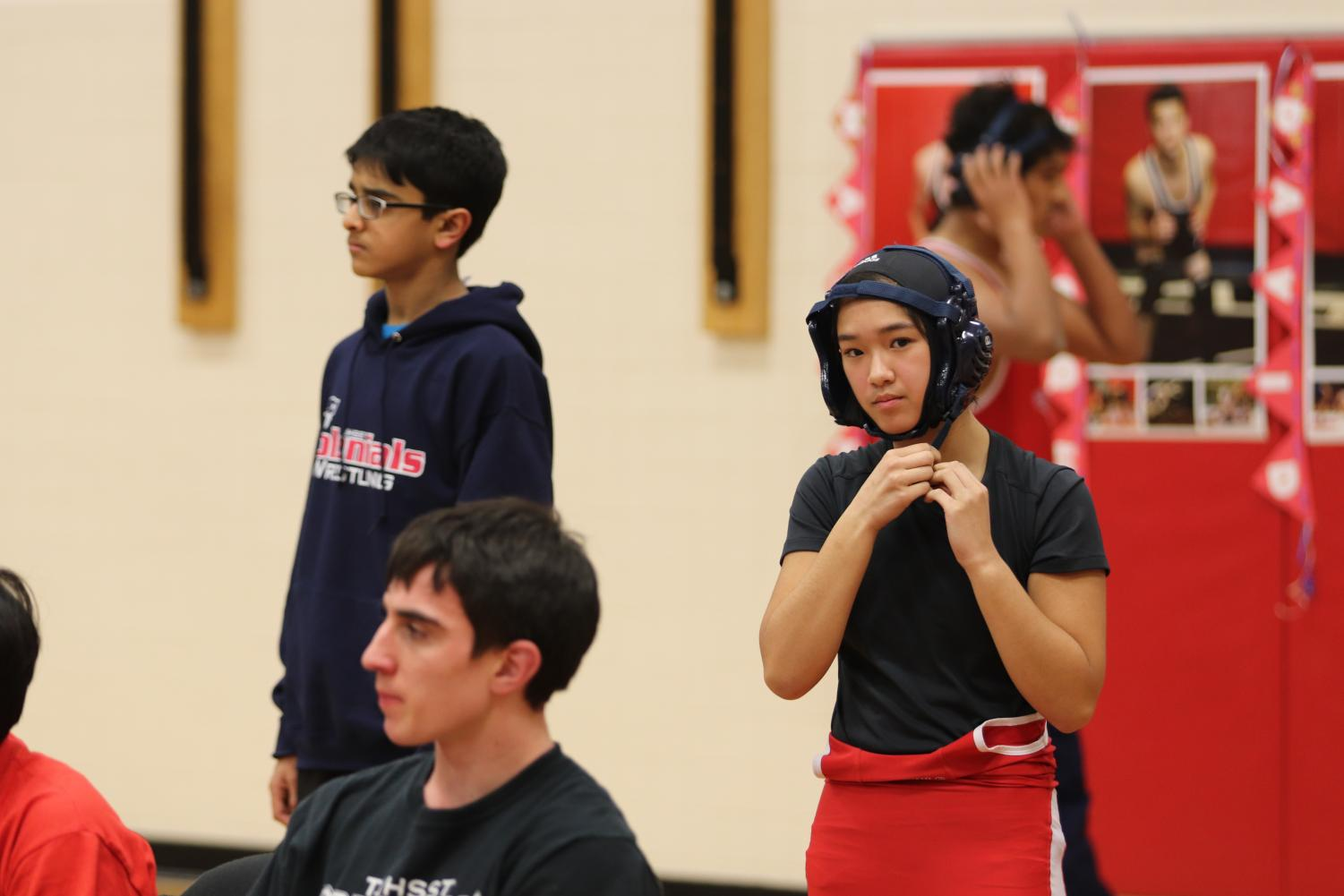 "In preparation for her upcoming match, freshman Brianna Ta puts on her ear guard. Despite being only one of two girls on Jefferson's varsity wrestling team and much smaller than many of her opponents, Ta placed third in National Districts and qualified for regionals. ""People are usually amazed [when they find out I do wrestling and jiu-jitsu]. My friends, actually, call me 'Tata Buff', and on the wrestling team, my nickname is 'Warrior Princess',"" Ta said."