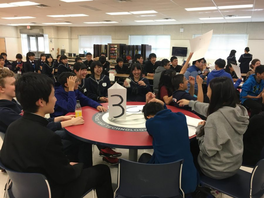 Visiting students from Fujishima High School laugh alongside Jefferson students as they rush to hold up their answer to a question.