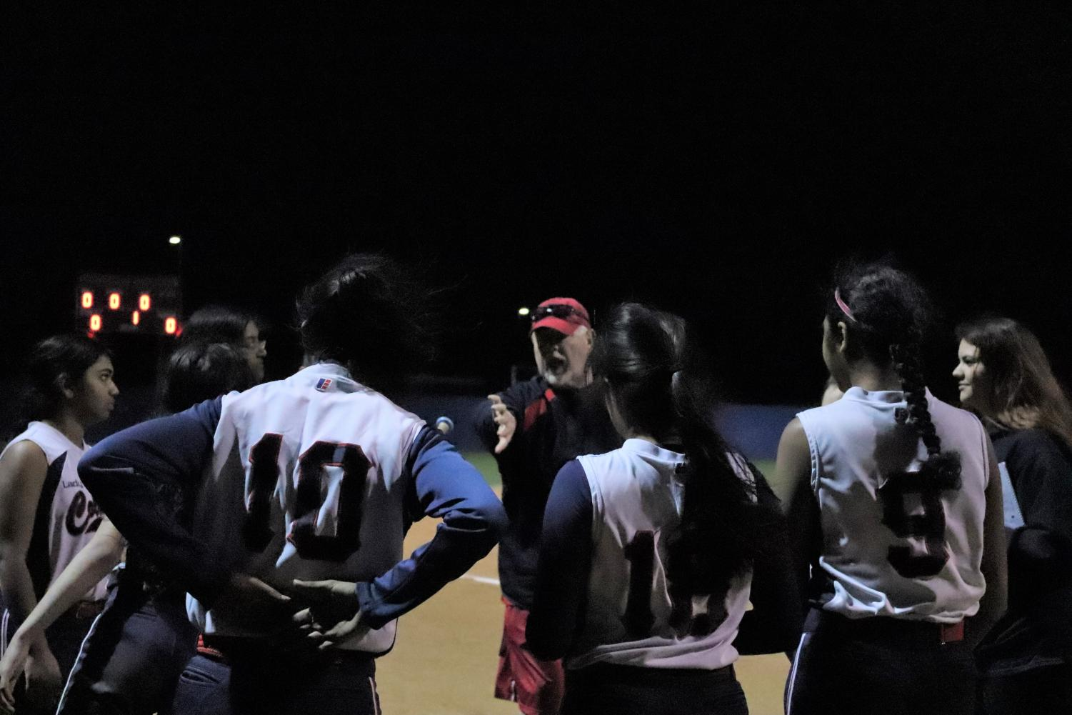 After+the+game%2C+Jefferson+players+and+coaches+huddled+up.+The+players+listen+as+head+Varsity+softball+coach+Mitchell+Hughes+talks+to+the+team+about+their+performance+during+the+game.