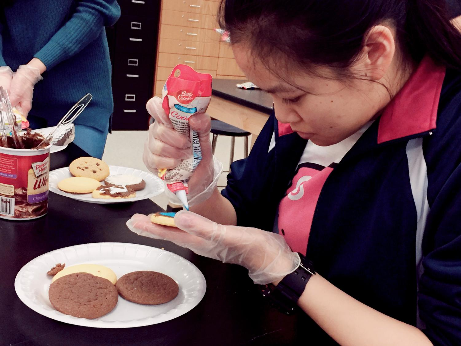Junior Jennifer Liu decorates a plate of cookies with icing after finishing her thank-you card.