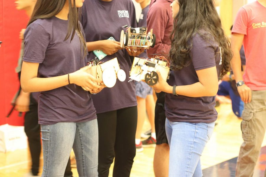 Holding their robots, freshmen converse with their friends before the competition.