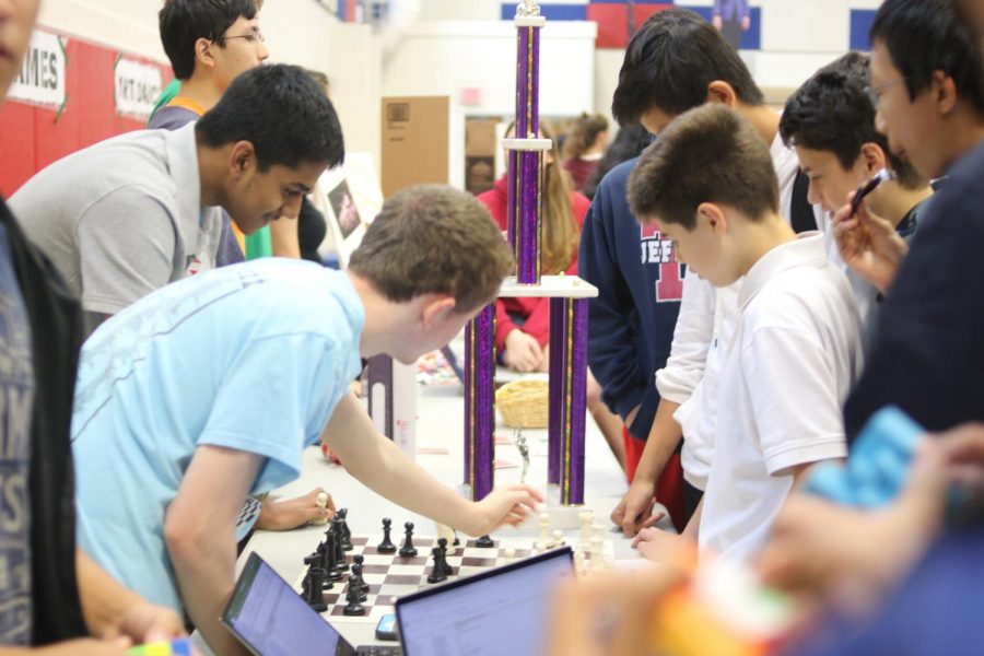 The TJ Chess Club discusses the game of chess as they prominently display a trophy.