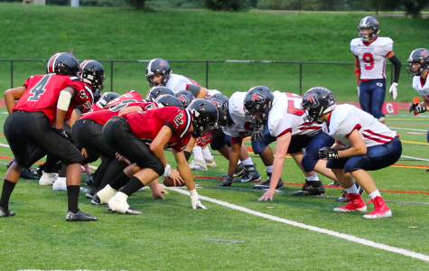 The Colonials and Mustangs wait for the play to start during their game on Aug 30th.