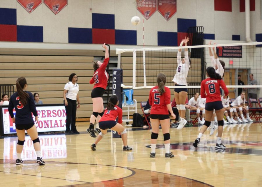 Senior Jenny Pruitt jumps to hit the ball back to Justice players.