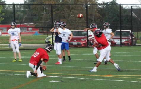 Having lost both games in the 2018-2019 fall season and with only a week left until the varsity football team's match against Manassas Park, starting quarterback senior Sohail Mohanty throws the ball to his wide receiver in a drill during football practice after school.