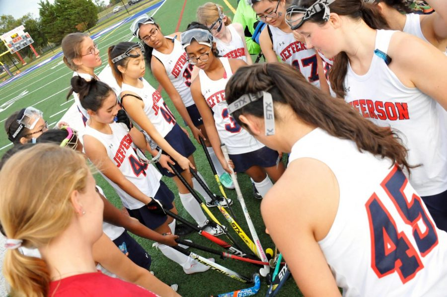 Listening+intently%2C+the+JV+field+hockey+team+huddles+around+the+coach%2C+Allie+Ivener%2C+before+a+game.%0A
