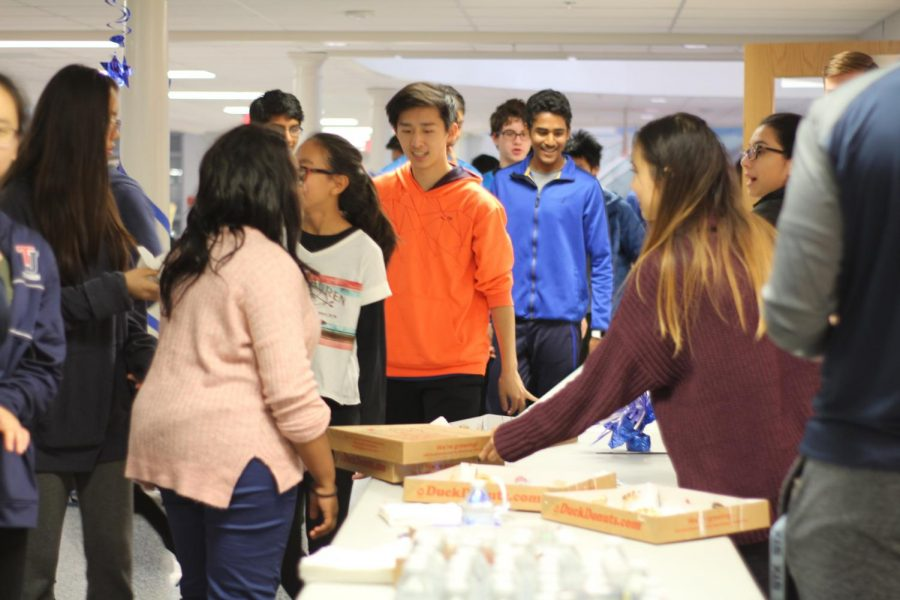 Junior+Sophia+Cheng+hands+out+complimentary+donuts+provided+by+SGA+to+students+attending+the+Gala.