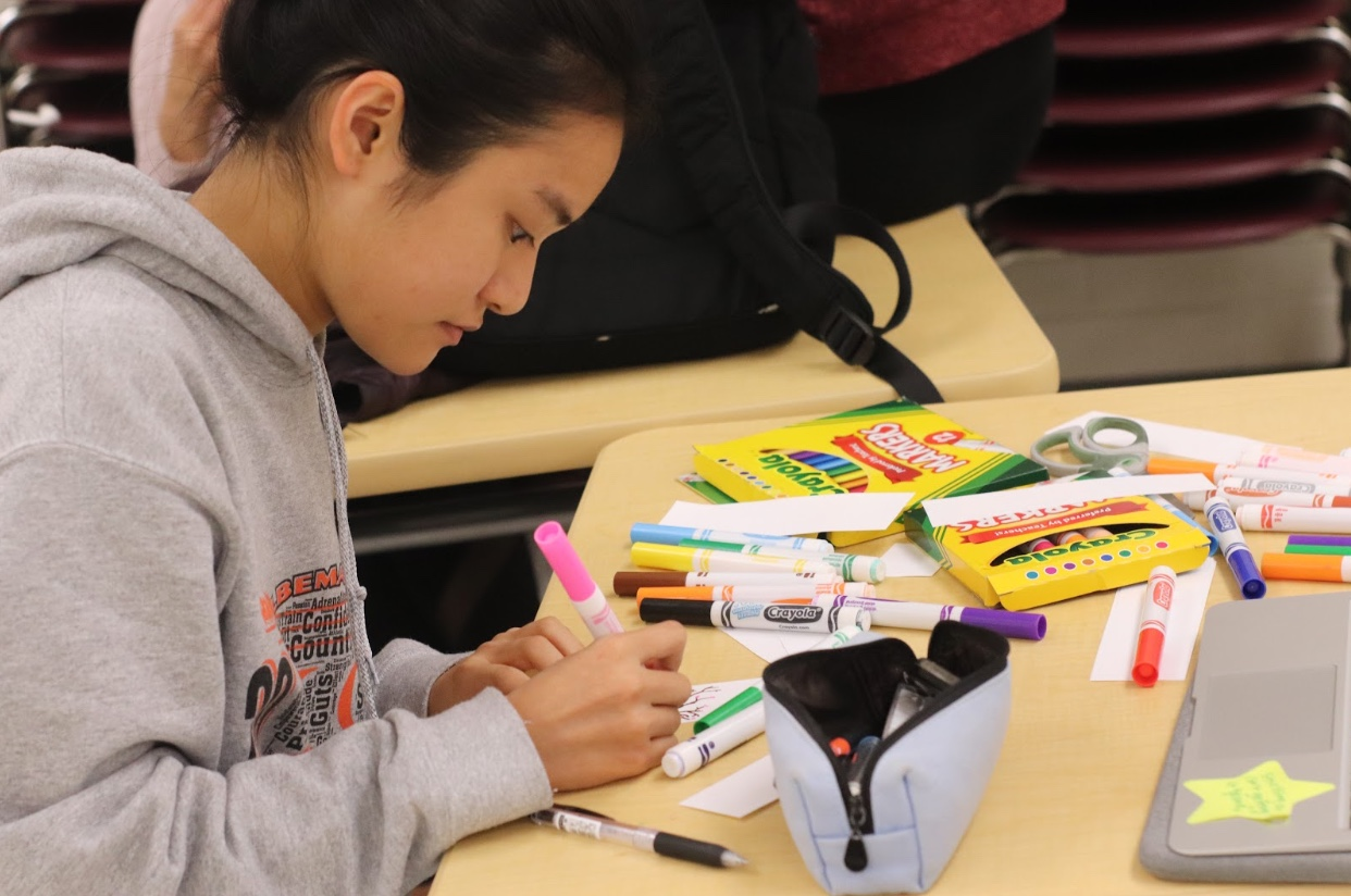 Senior Lilia Qian draws a tree onto a bookmark, while participating in the NHS Holiday Service Project.