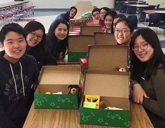 Members of Fellowship of Christians package gifts into shoeboxes to be shipped to children in other countries.