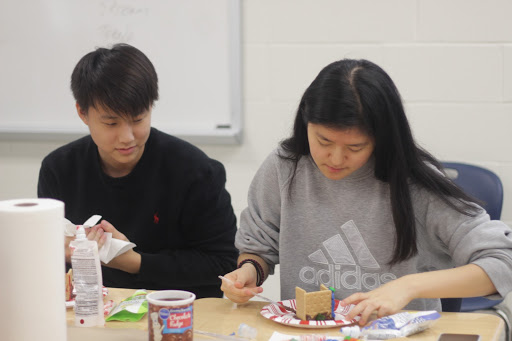 Senior Jongwan Kim watches senior Mina Kim construct the frame of her gingerbread house at Amnesty International's annual Gingerbread Jail House.