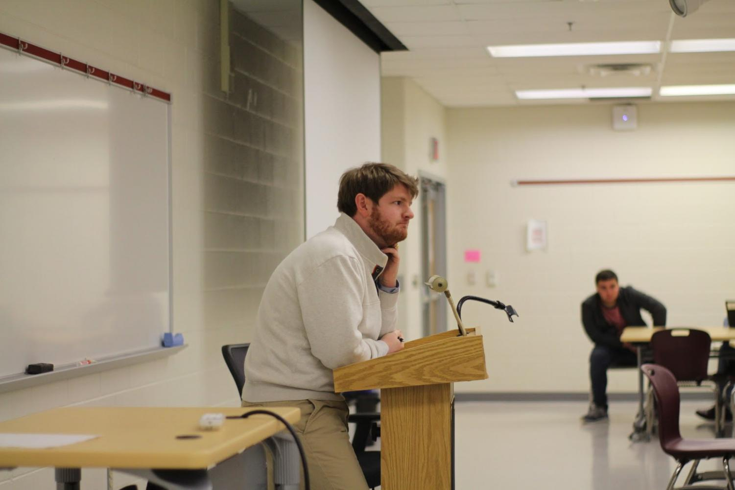 Guest speaker Kyle McDaniel  lectures on Trump's policies.