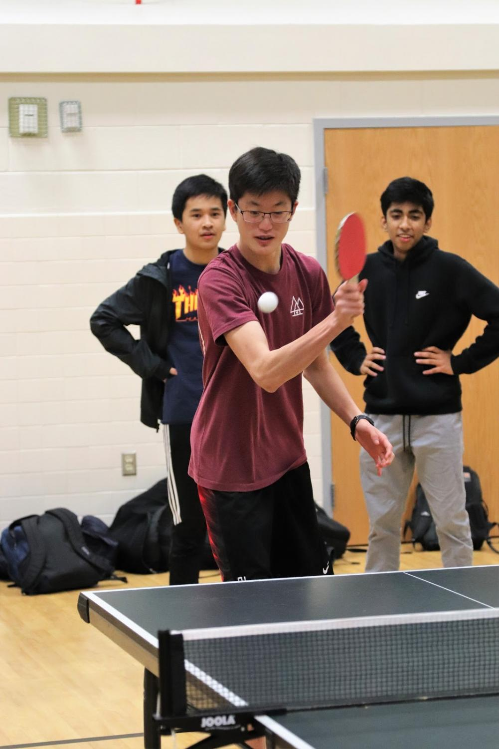Ready for action, freshman Andrew Kim attempts to knock back the ball coming at him. Freshman Shreyas Chennamaraja and Alex Peal watch in the background as they wait for their match to begin. Photo courtesy of Forrest Meng.