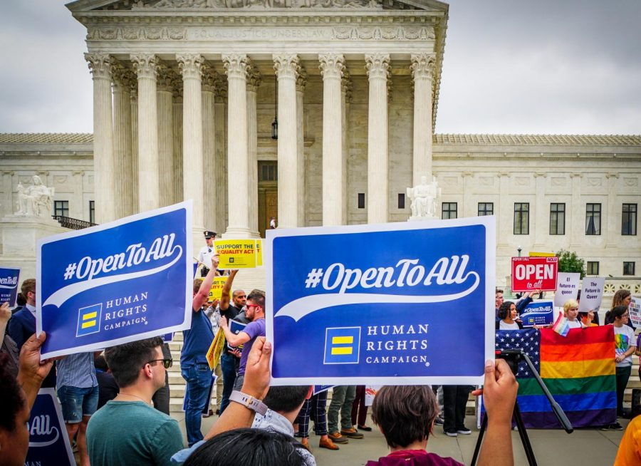 Protesters outside of the Supreme Court rally in favor of the same-sex couple alleging discrimination against a baker who cited his religion when refusing to make them a wedding cake.