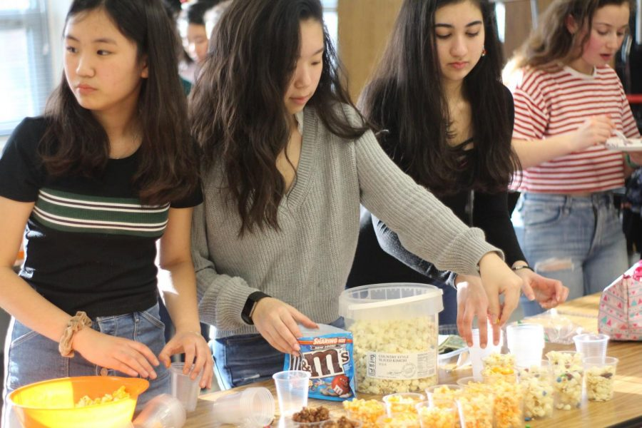 "Sophomores Katherine Jia, Minjoo Song, Vyomika Gandhi, and Alexandra Friedman dish out colorful cups of different types of popcorn. These included regular buttered popcorn, caramel popcorn with m&ms, mint chocolate popcorn, and cheese popcorn. ""I enjoyed being able to take part in the FBLA Marketplace, as it was a great way for people to learn how to market and sell things,"" Jia said."