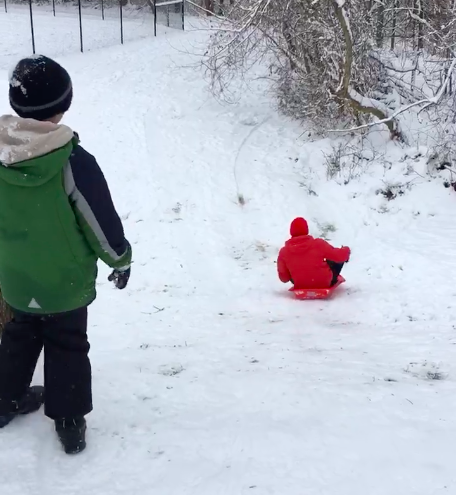 Freshman Nicolas Tiongson sleds down a hill while his brother watches